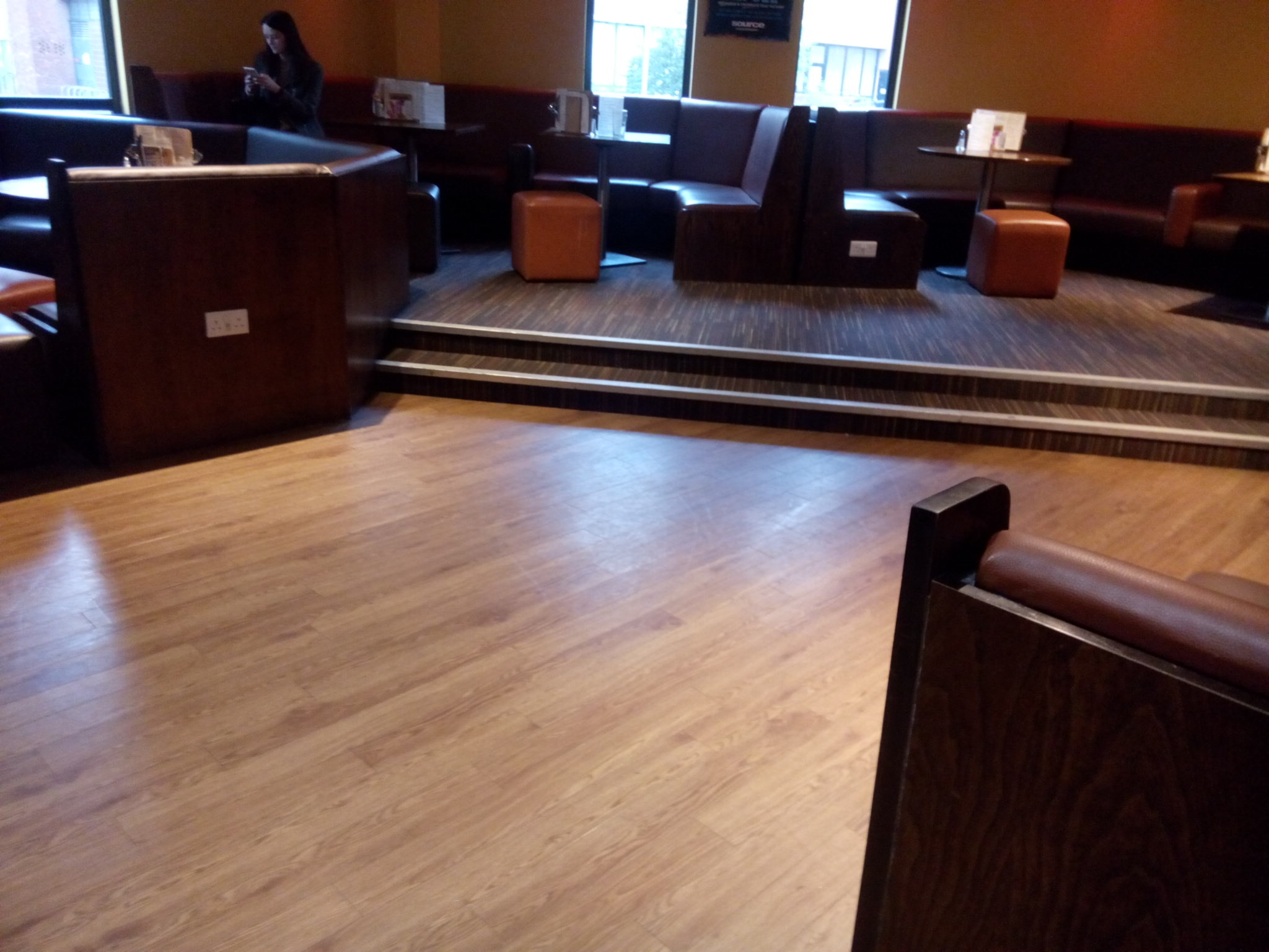 Bar area showing seating on a level surface, and up two small steps.